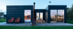 Black cabin with outdoor deck and chimney