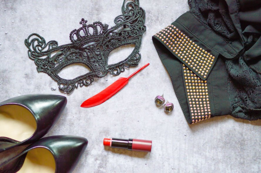 flat lay of a black shirt, a black lace mask, black heels, red lipstick and a red feather