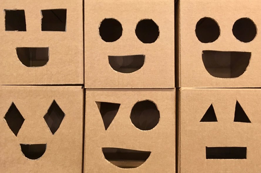 six cardboard boxes with smiley face cut-outs