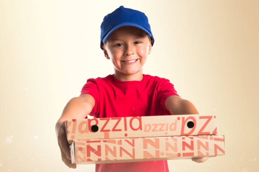child holding pizza boxes