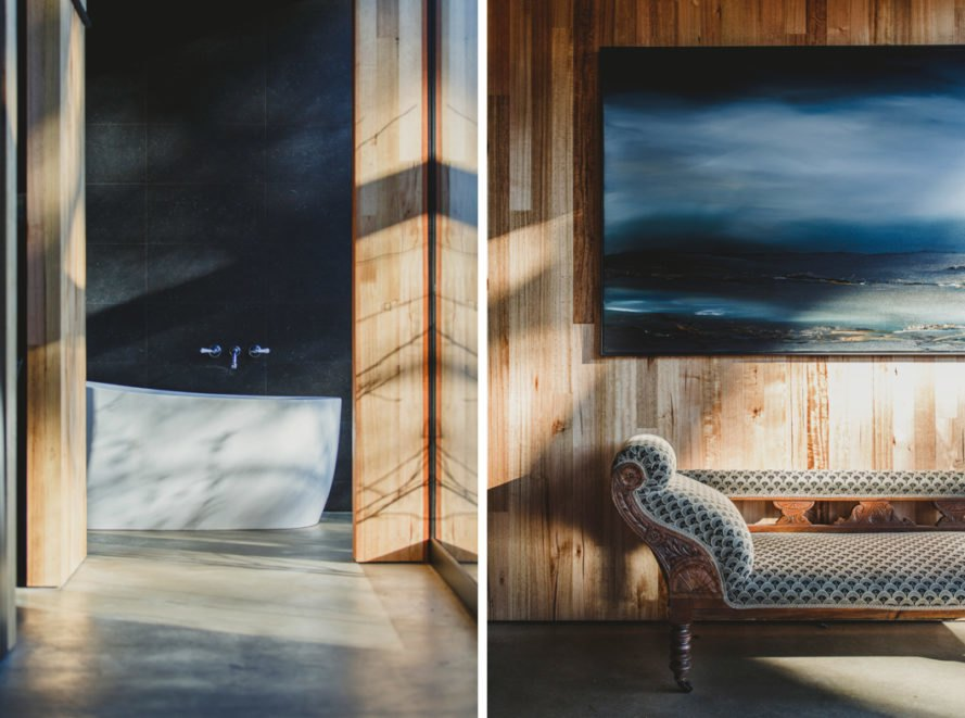 On the left, white bathtub in black bathroom. On the right, antique chaise under a painting.