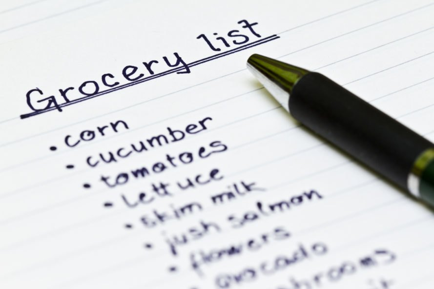 pen on top of a grocery list