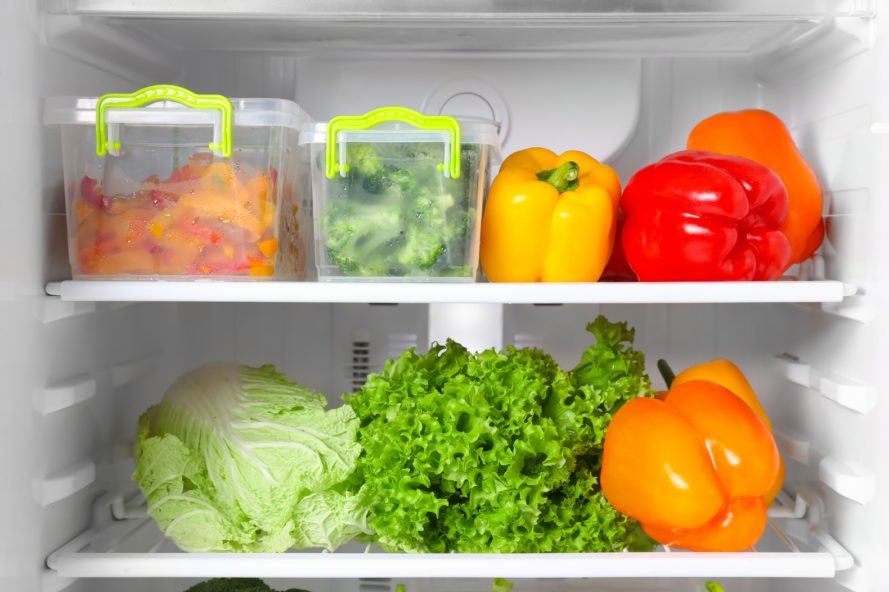 fresh vegetables and containers with chopped vegetables inside a refrigerator