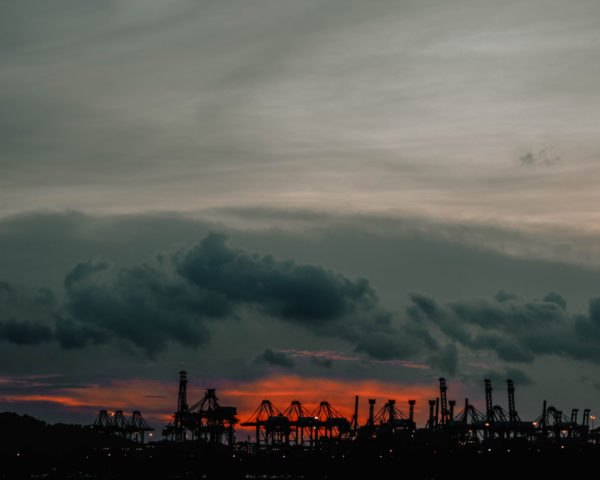 factories and oil drillers at sunset