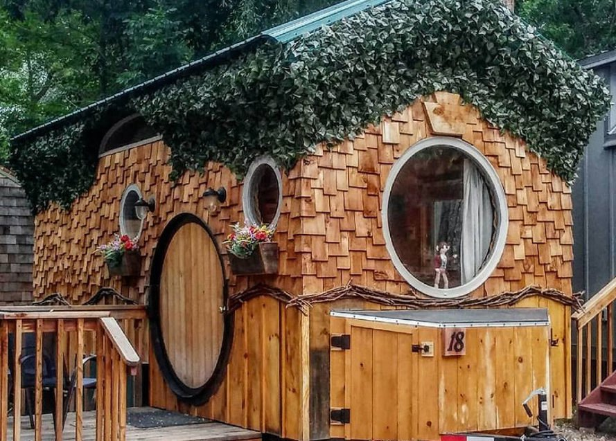 wooden tiny home with moss-covered roof