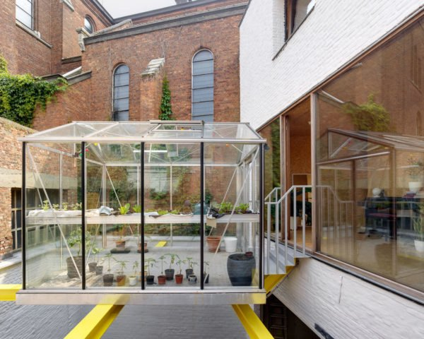 greenhouse on yellow beams behind a white and brick home