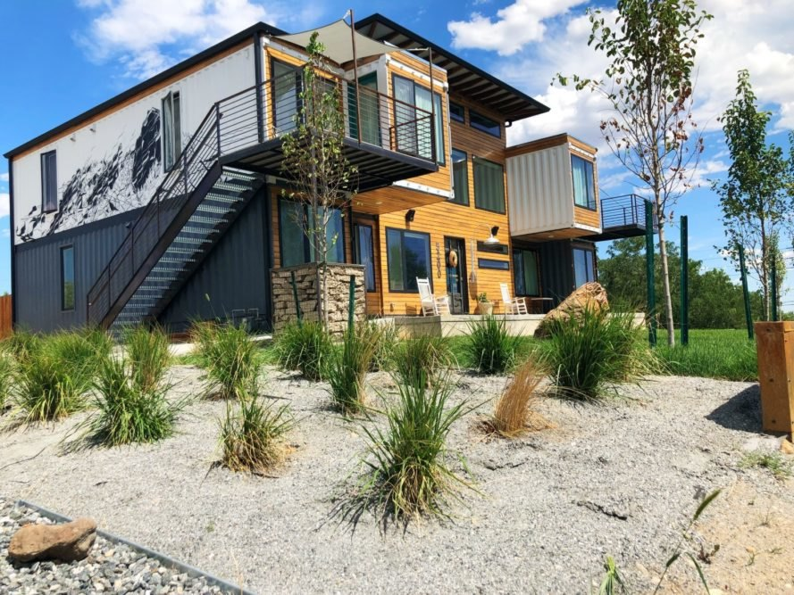 black and white shipping container home with landscaping