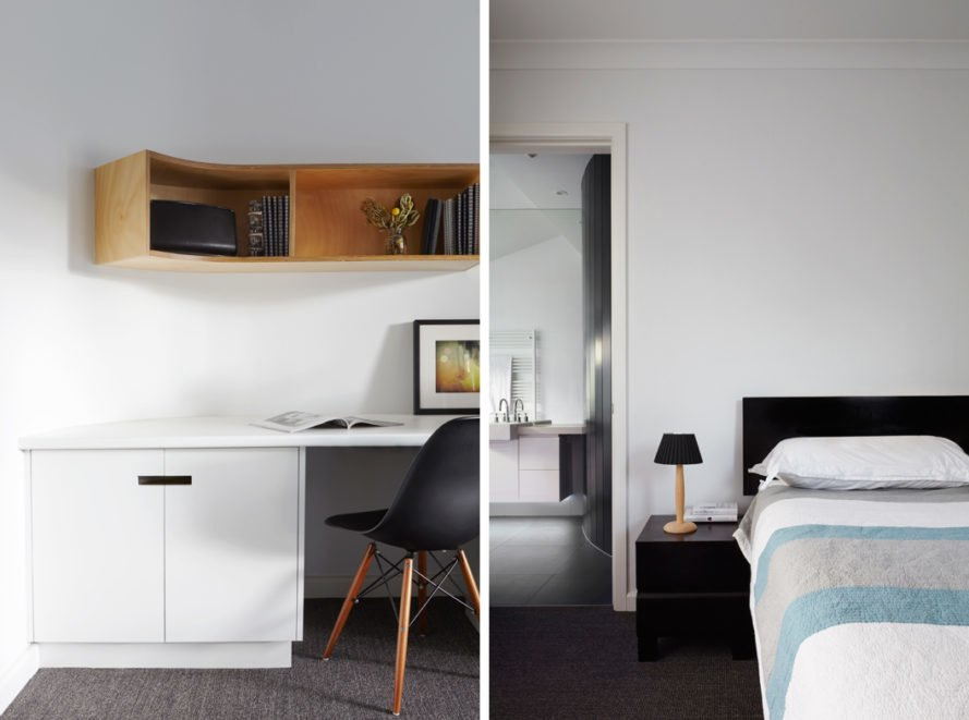 white bedroom with black headboard, gray and blue bedding and a white desk