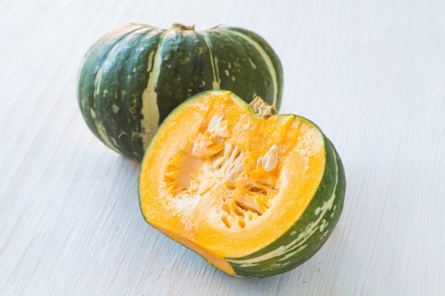 one whole green kabocha squash and half of a kobocha squash with yellow flesh and seeds showing