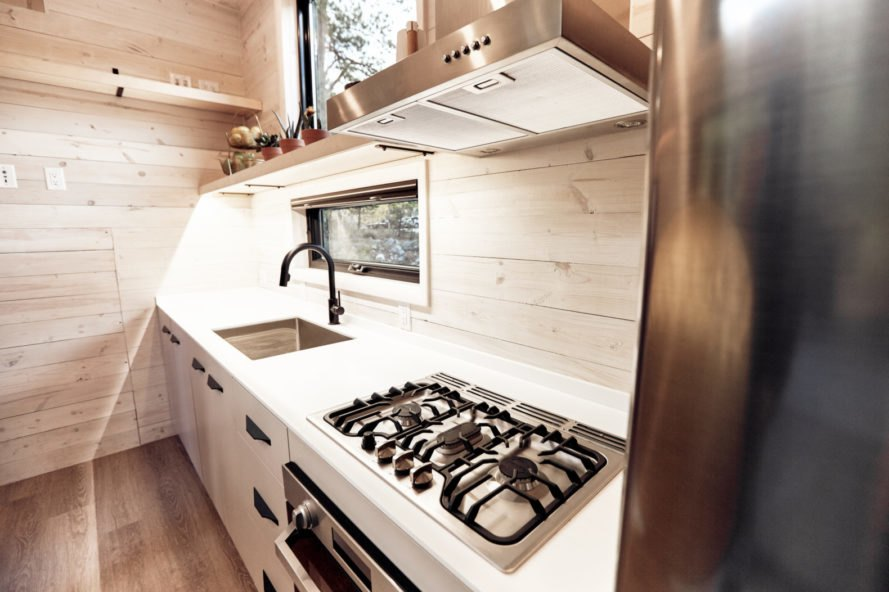 wood-lined kitchen space with stove top and sink