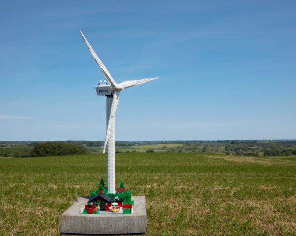 wind turbine above a cottage all made from LEGOS outside in vast green lot under blue skies