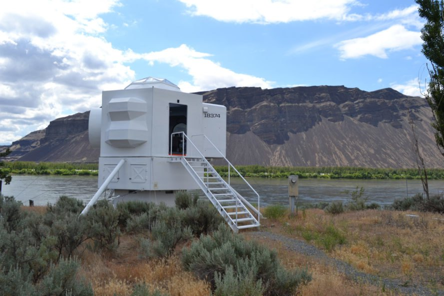 white spaceship-shaped tiny home near mountains