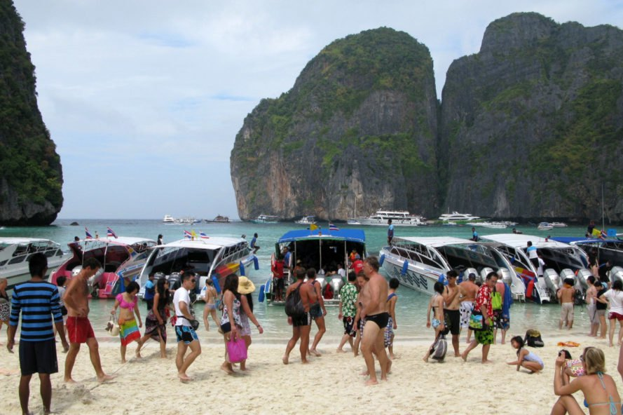 Crowds of people on sand and several boats in water at Maya Bay