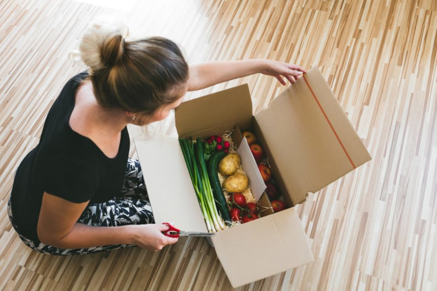 woman opening a box of produce