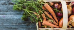 wicker basket filled with carrots and onions