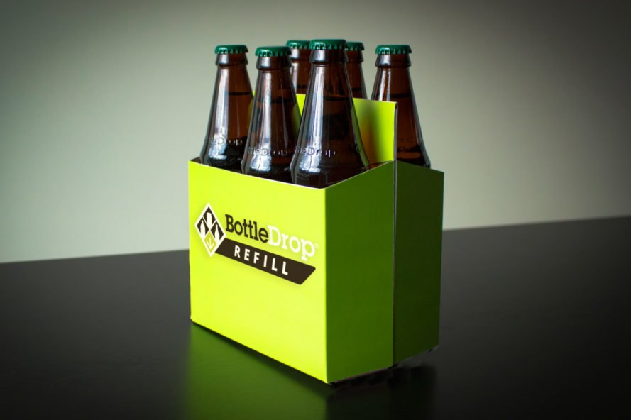 "refillable beer bottles in green cardboard carrier that reads, ""BottleDrop Refill"""