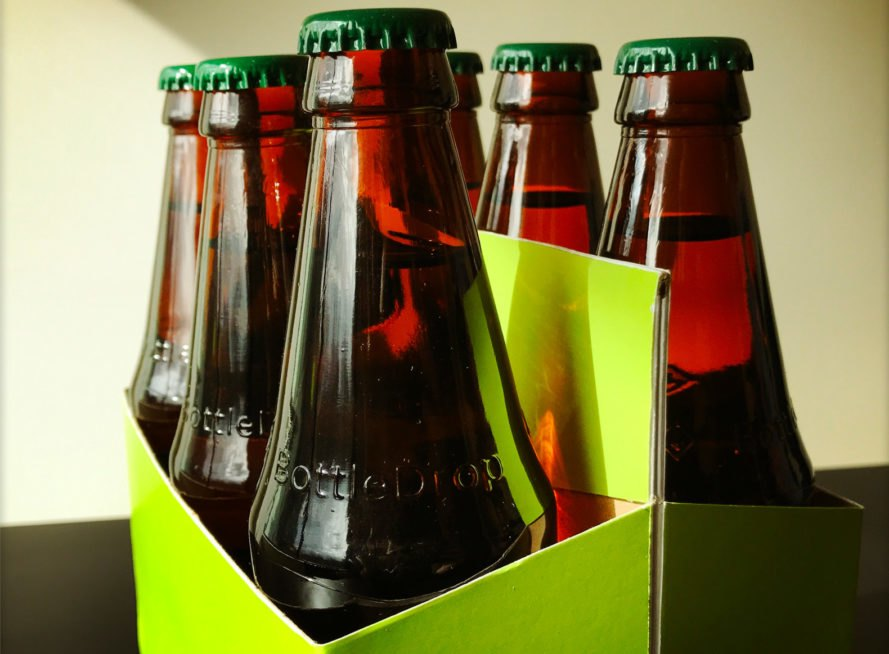 beer bottles with green caps in green cardboard carrier
