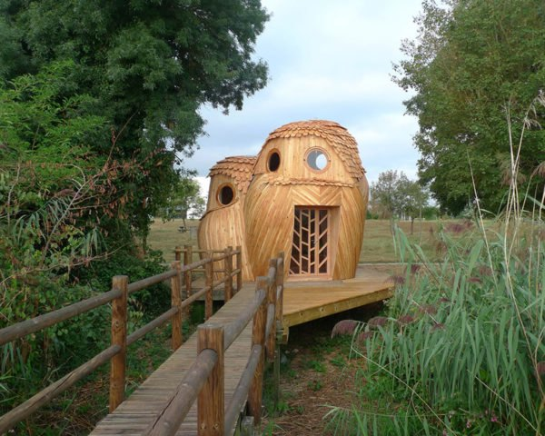 wood walkway leading to wood tiny home in the shape of two owls