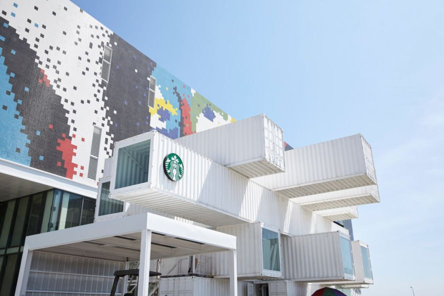 cantilevered, stacked white shipping containers with starbucks logo