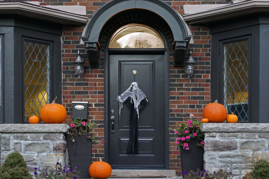 porch of brick home with skeleton on the door and pumpkins on the porch