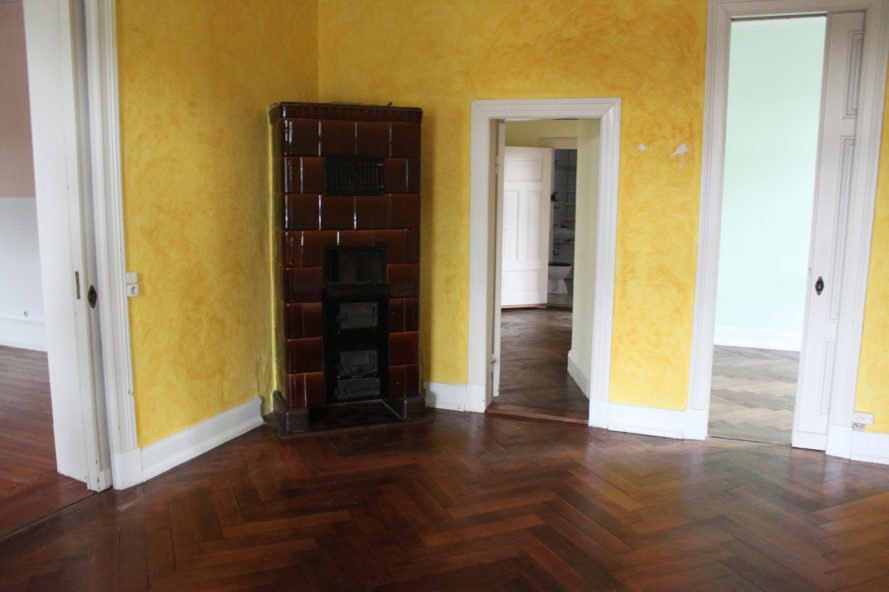 brown masonry heater in the corner of a yellow room