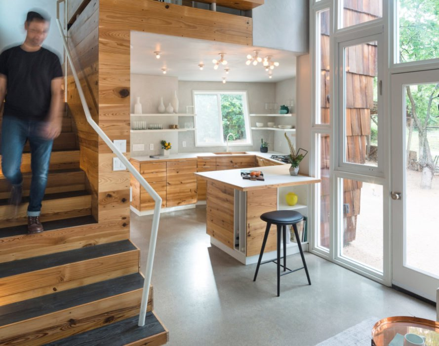 man walking down stairs into living room and open kitchen