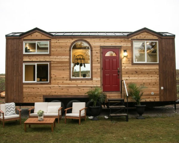 wooden tiny home with red front door
