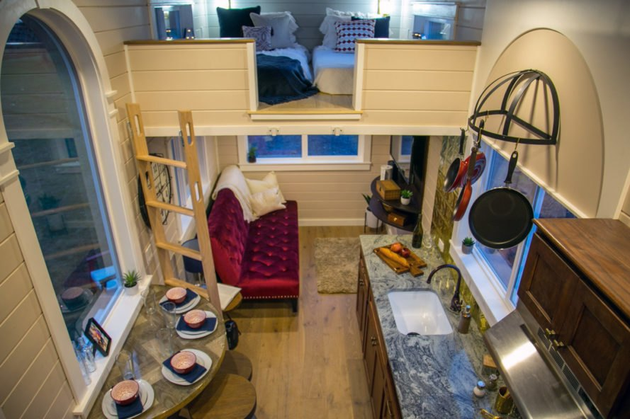aerial view of tiny home with kitchen, small dining set and red velvet tufted sofa