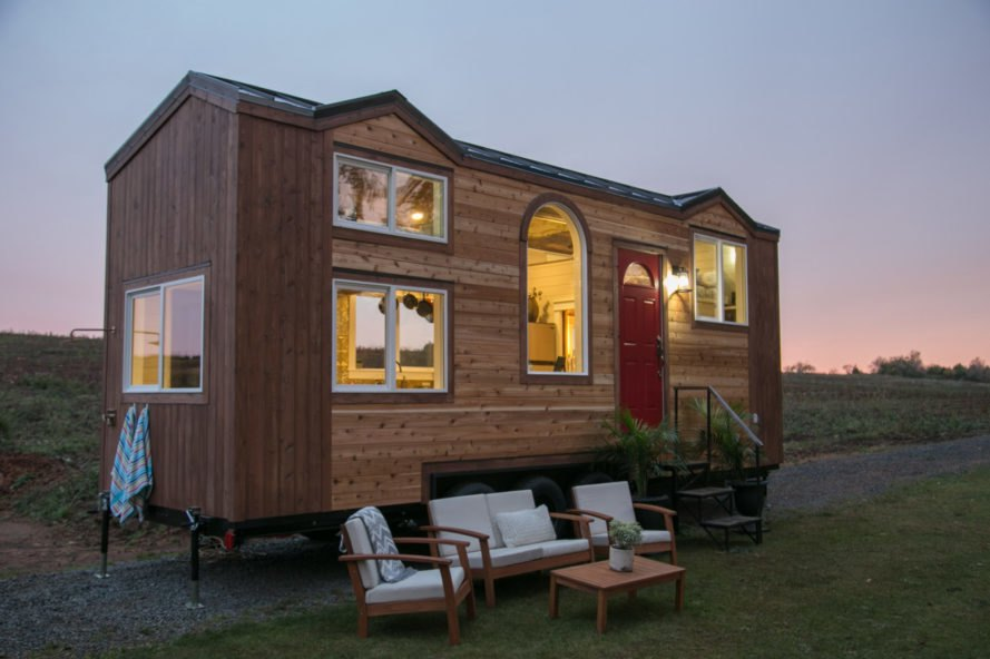 angled view of wooden tiny home with red front door at dusk