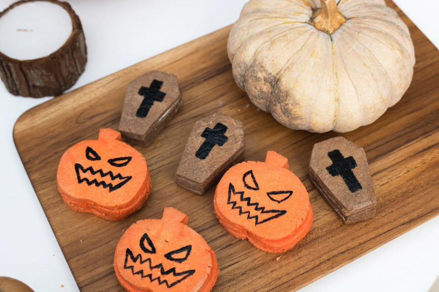 cookies shaped like pumpkins and coffins on a wood board