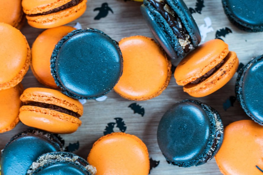 Orange and black macaroons on a table