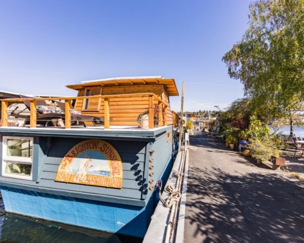 a blue houseboat on a dock
