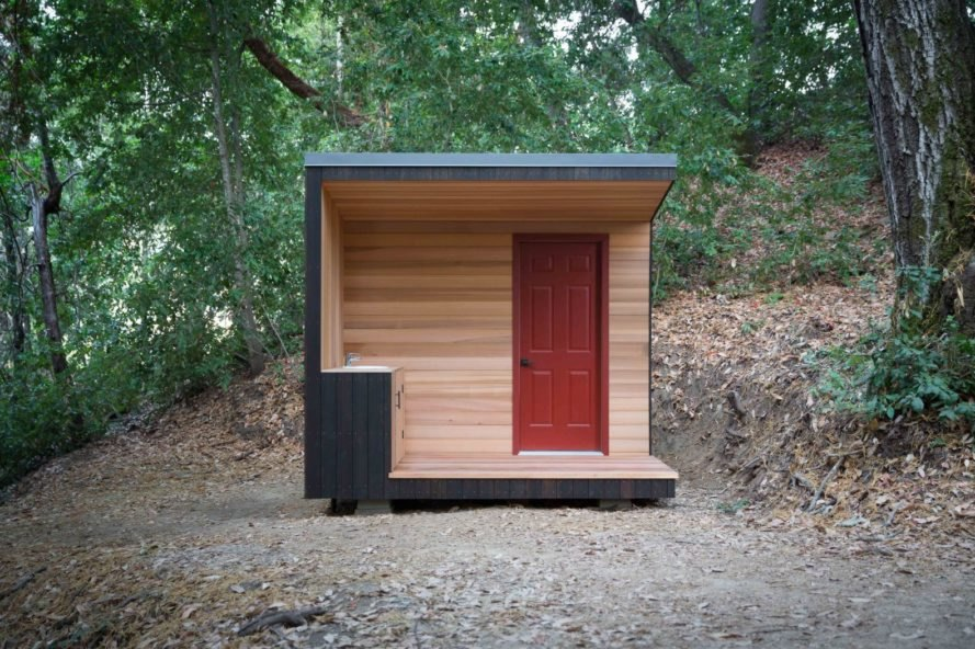 a cube like outhouse with red door