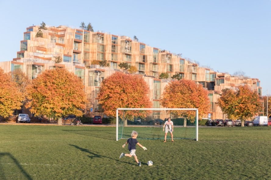people playing soccer in a green field in front of large apartment building