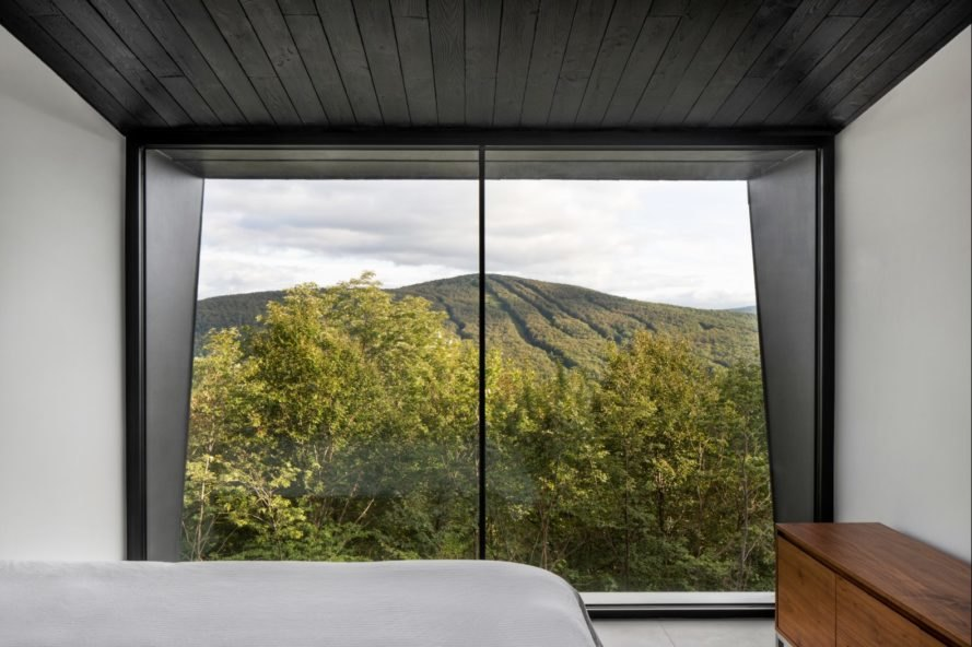 bedroom with glass window looking out over forest