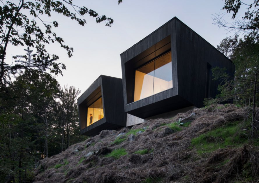 two black boxy cabins with glass facades