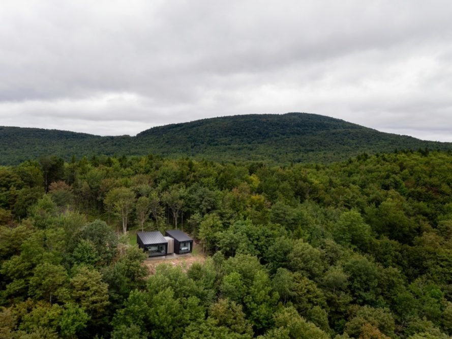 aerial view of two black cabins in a forest
