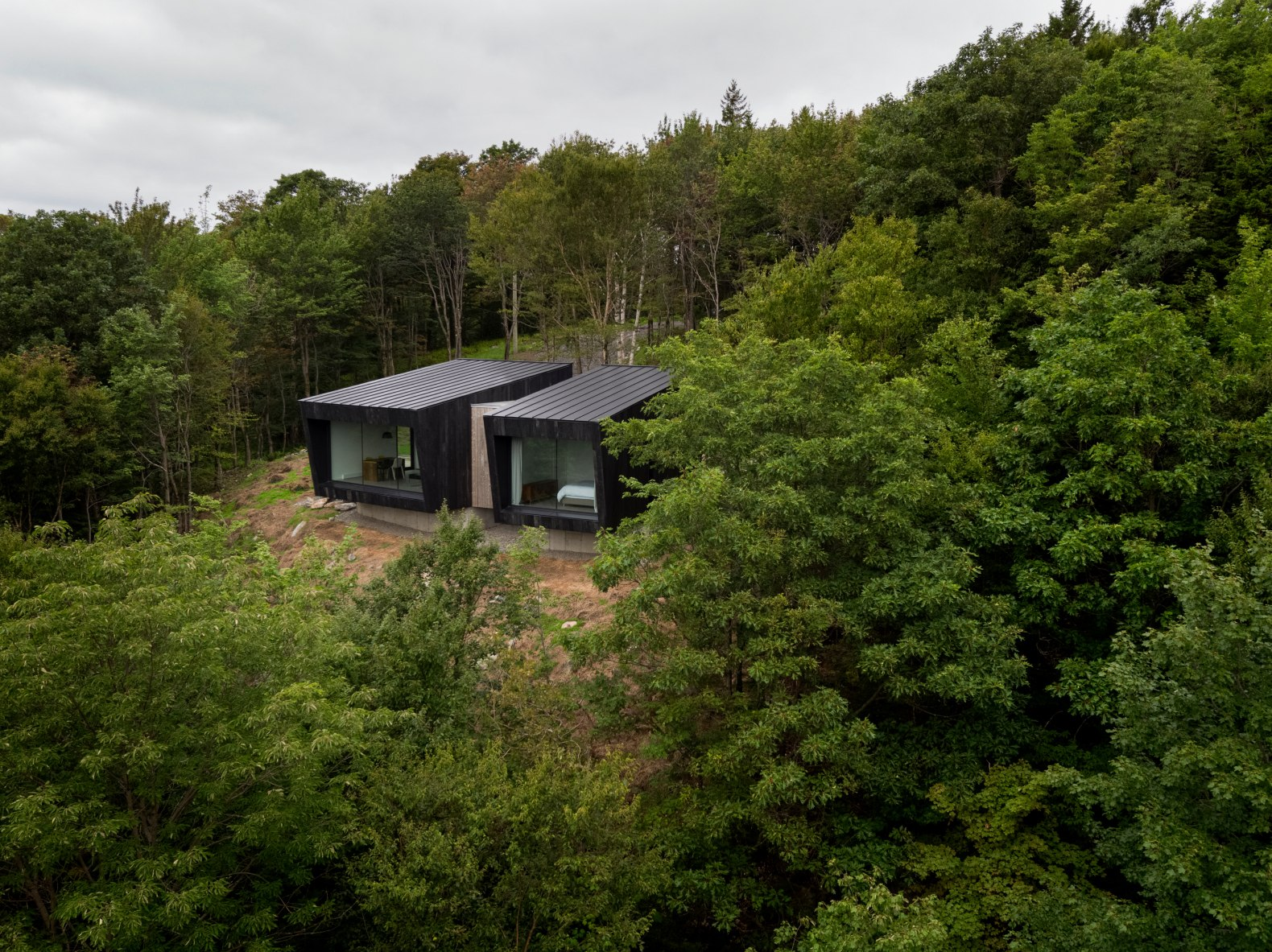 Two moody, tranquil cabins perch above a Quebec forest