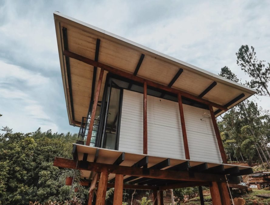 a slated roof covers a tiny glass and wood cabin