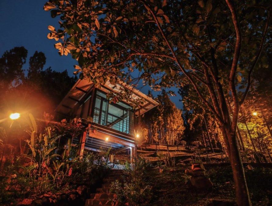 a two-story cabin illuminated at night