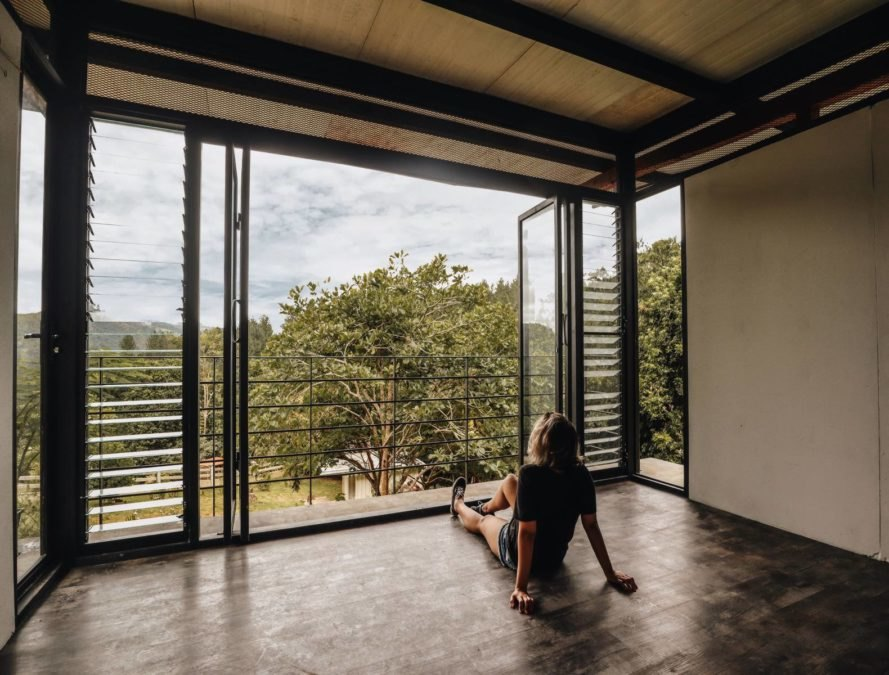 a woman on the floor looking out into a forest view