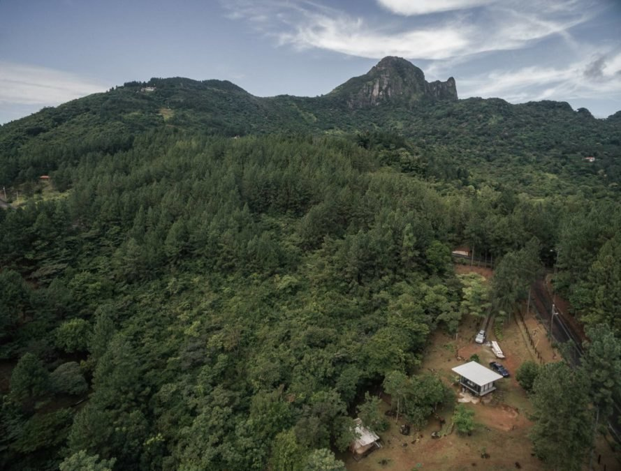 aerial view of wood and glass cabin surrounded by forest