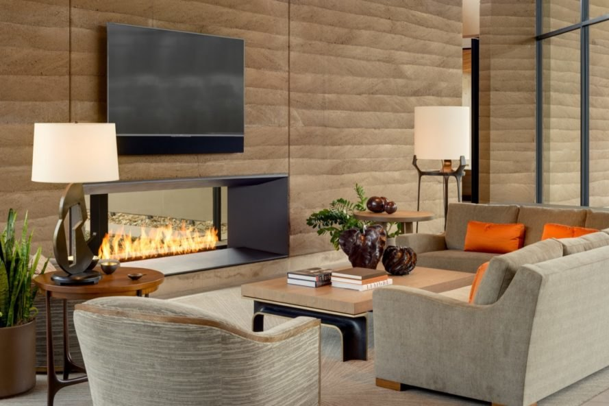 gray couch with orange pillows facing a fireplace