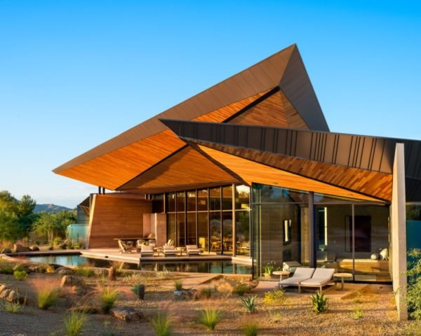 geometric angled roofs on rammed earth home