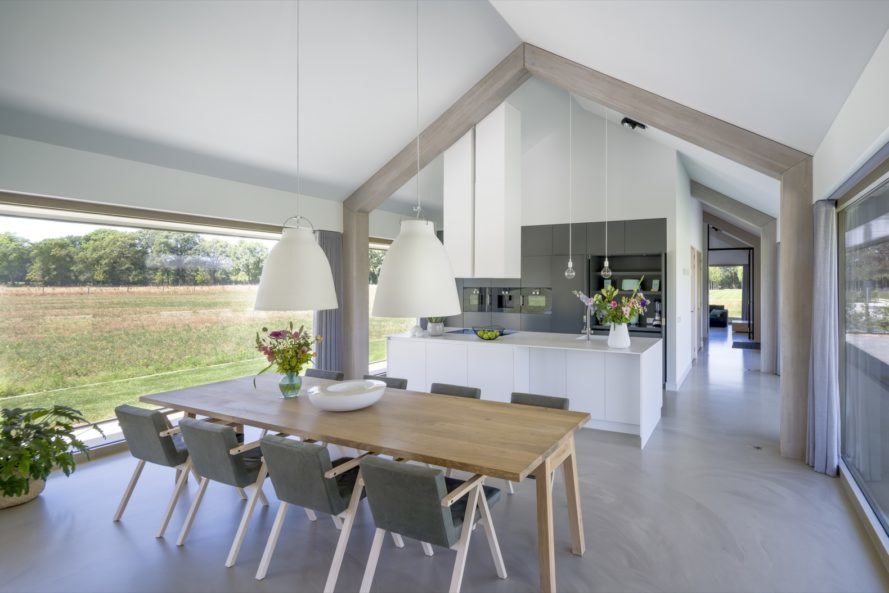 white interior with light wood dining table and white kitchen