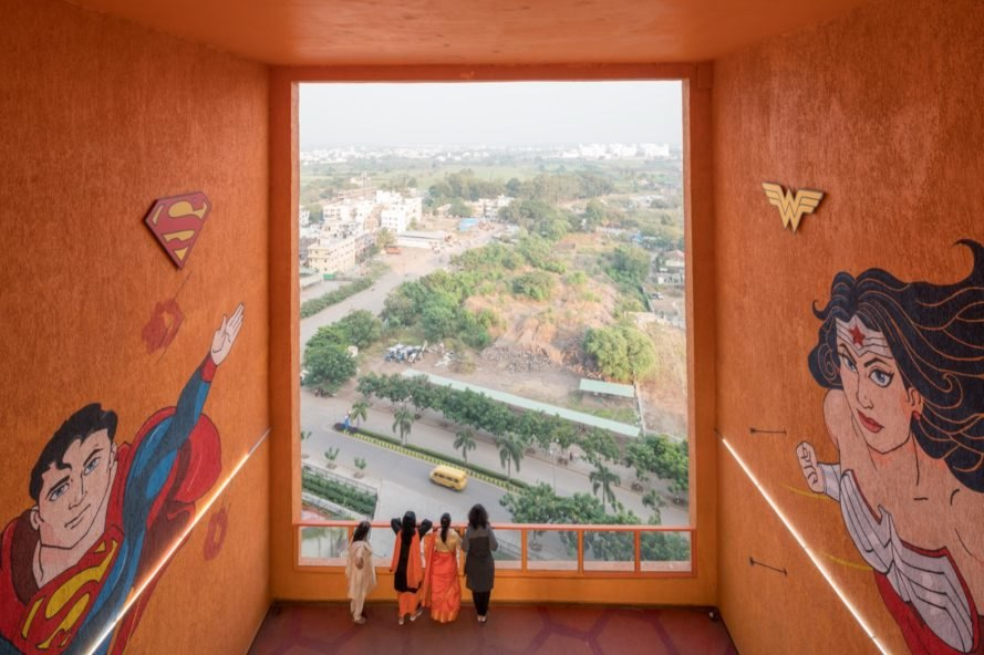 orange room with superhero murals and city views