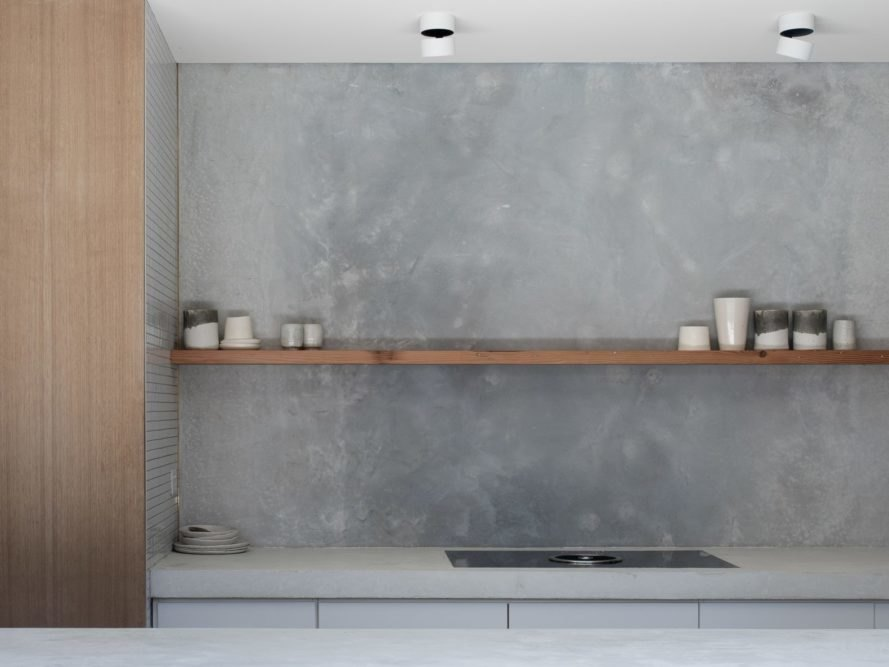 concrete and marble kitchen with thin wooden shelf