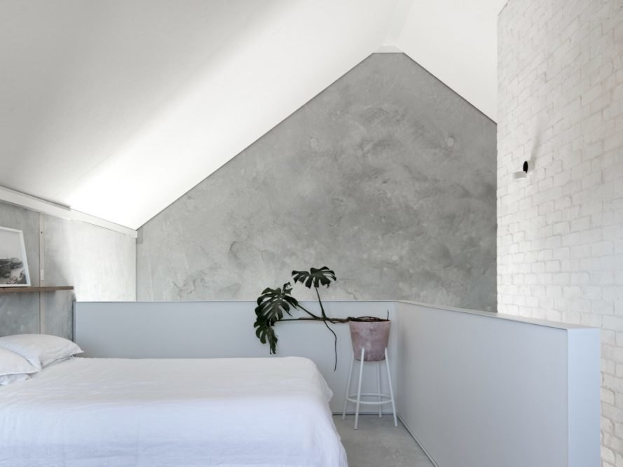 concrete walls with white bed