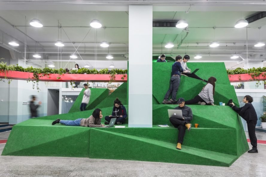 tall green geometric volume with people sitting, standing and lying on the structure
