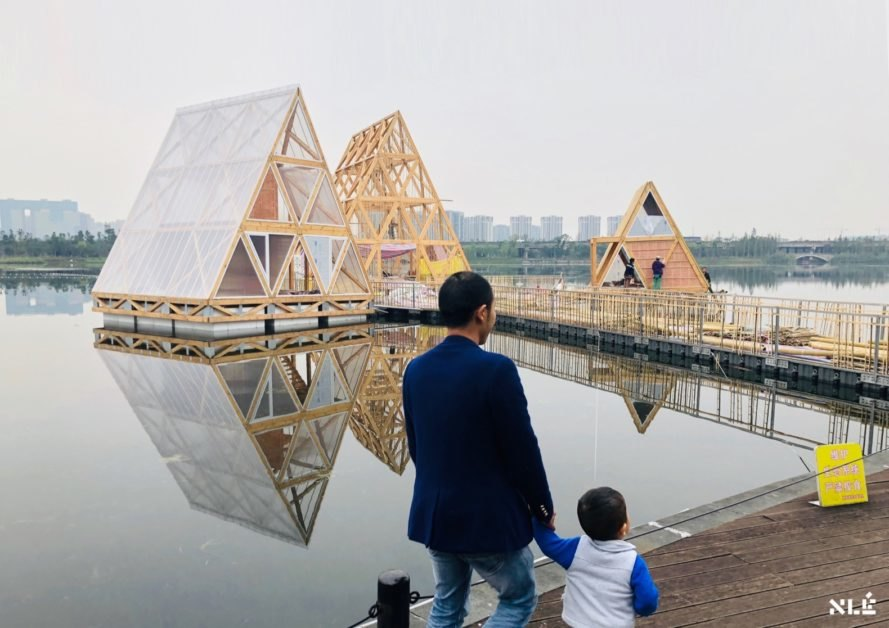 man and child walking near floating wood structures